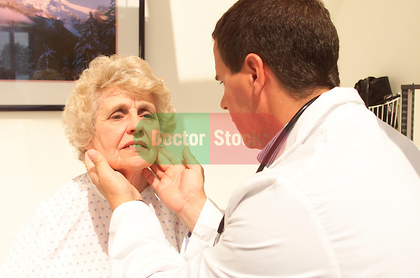 young male doctor conducting a routine examination of an older, elder female patient, feeling her glands