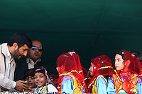 A group of local children, dressed in ethnic uniform, meet the Iranian President Mahmoud Ahmadinejad on his trip to the western province of Kermanshah.