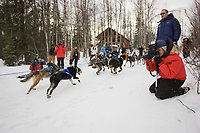 Spectators watch Rohn Buser as he heads off Willow Lake at the restart of the 2008 Iditarod in Willow, Alaska