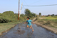 A child plays in a road that has been flooded with industrial wastewater from a nearby water channel. The water is laced with toxins from the leather-treatment process and is discharged directly into local waterways and onto farmland.