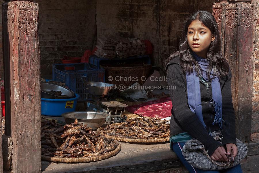 Nepal, Kathmandu.  Young Woman Waiting at a Shop Selling Dried Fish.