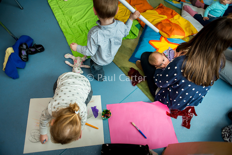 "A mother breastfeeding her baby at a drop-in breastfeeding support centre while another child does some drawing next to her.<br /> <br /> Image from the ""We Do It In Public"" documentary photography project collection: <br />  www.breastfeedinginpublic.co.uk<br /> <br /> Dorset, England, UK<br /> 17/04/2013"