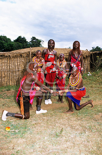 Lolgorian, Kenya. Young Moran Siria Maasai proposing marriage to his girlfriend with two other couples.
