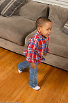 Two year old toddler boy walking looking to side