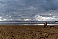 Two dog walkers on the beach