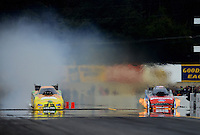 Oct. 7, 2012; Mohnton, PA, USA: NHRA funny car driver Johnny Gray (left) and Bob Tasca III engaging in a pedal fest resulting in a side by side funny car fire show during the Auto Plus Nationals at Maple Grove Raceway. Mandatory Credit: Mark J. Rebilas-