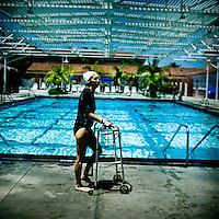 73 year old Margo Bouer uses a frame to help her walk before Aquadette practice at Laguna Woods, California. Margo suffers from severe MS, but says her nausea and shaking almost disappear when she is in the swimming pool. She has been with the Aquadettes for 16 years. The Aquadettes are a group of women ageing from their early 60s upwards who meet to practice synchronised swimming. Every year, they practice together, they make costumes together, they swim together, and at the end, they perform together.