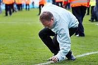 A Manchester City supporter removes part of the pitch as a souvenir after the Premier League match between Manchester City and Swansea City at the Etihad Stadium, Manchester, England, UK. Sunday 22 April 2018