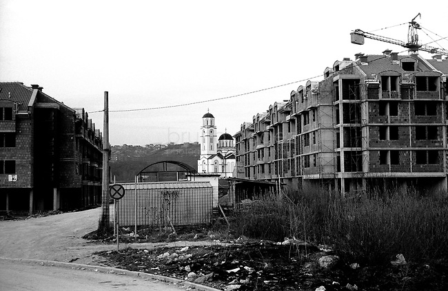 BOSNIA-HERZEGOVINA, Belgrade-Sarajevo Road, 03/2003..Lanscape pictures taken from the bus at Sarajevo. .The bus stops at the station who takes place in the Srpsjko Sarajevo (ex muslim quarter of Lukavica), a quarter of very new buildings and new churches..We are ten kilometers far from the old center of Sarajevo. The bus doesn't run anylonger. .BOSNIE-HERZEGONVINE, Route Belgrade-Sarajevo, 03/2003..Photo prise depuis le bus qui relie Belgrade à Sarajevo. Le bus s'arrete à la gare routière de Srpsjko Sarajevo (ex quartier musulman de Lukavica), un quartier où l'on construit de nouvelles habitations et de nouvelles églises. Le centre historique de Sarajevo est encore à 10 kms mais le bus ne va pas plus loin..© Bruno Cogez