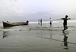 Fishermen in Cartagena, Colombia strain to pull in their net.