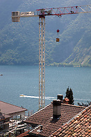 Switzerland. Canton Ticino. Lugano. Castagnola area. Construction of a private house on a deluxe standing. The crane belongs to the Garzoni company. Tiled roofs. View on the lake of Lugano ( also called Lago Ceresio). Private boat on the lake. 2.06.12 © 2012 Didier Ruef