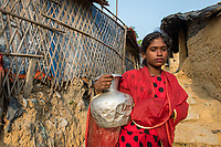 Bangladesh, Cox's Bazar. Kutupalong Rohingya Refugee Camp. The Rohingya, a Muslim ethnic group  denied citizenship in Burma/Myanmar have escaped persecution from Burmese militants in their country. There are up to 500,000 refugees and migrants living in makeshift camps in Cox's Bazar. Girl in red with water jug.