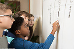 Public elementary school for gifted children grades K-6: Science lab students entering data from different groups on dry erase board