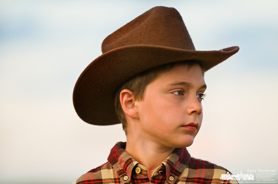 Boy, 8-11, wearing cowboy hat stands in a field of wheat straw bales on a farm