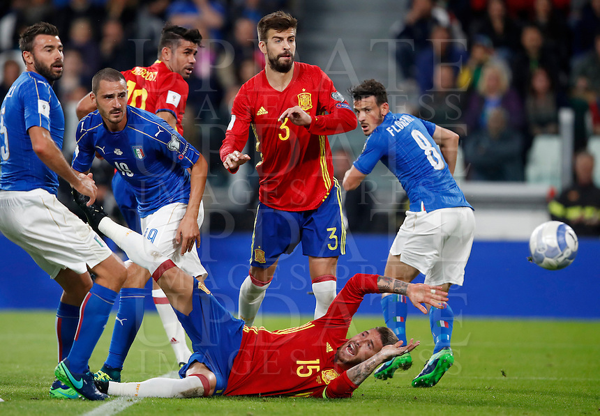 Spain Sergio Ramos, bottom, falls on the pitch last his teammates Spain's Diego Costa, center, Gerard Pique', second from right, and Italy Andrea Barzagli, left, Leonardo Bonucci, second from left, and Alessandro Florenzi, during the Fifa World Cup 2018 qualification soccer match between Italy and Spain at Turin's Juventus Stadium, October 6, 2016. The game ended 1-1.<br /> UPDATE IMAGES PRESS/Isabella Bonotto