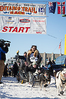 Mike Santos and team leave the ceremonial start line at 4th Avenue and D street in downtown Anchorage during the 2014 Iditarod race.<br /> Photo by Jim R. Kohl/IditarodPhotos.com