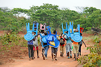 ANGOLA Kwanza Sul, village Kassombo, children on way to school, each child must bring his own plastic chair as the schools in poor condition due to the civil war and corruption, the revenues from oil rich Angola seems not reach the villages, one boy wears a T-Shirt with image of Barrack Obama / ANGOLA Kwanza Sul, Dorf Kassombo, Kinder mit Plastikstuehlen auf dem Weg zur Schule durch Felder des Dorfes, da die Schulen durch den Buergerkrieg zerstoert und ohne Inventar sind, muss jedes Kind seinen Plastik Stuhl mitbringen