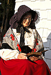 A lady wearing a bonnet reading a book outside