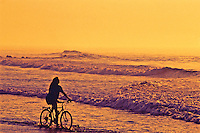 Woman riding bike along the beach at sunset.