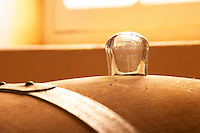 A barrique barrel in the wine cellar with a traditional glass stopper. Good to use if there is still some slow fermentation going on - Chateau Haut Bergeron, Sauternes, Bordeaux