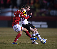 Taylor Kemp (2) of Maryland passes the ball away from Ryan Smith (4) of Louisville during the game at Ludwig Field in College Park, MD.  Maryland defeated Louisville, 3-1.