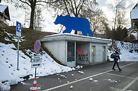 Switzerland. Canton Bern. Bärau. Winter time. Snow on the grass. A wooden blue bear sculpture and a student waiting for a bus. Graffiti on concrete walls. Parking signs. Bärau is a village in the municipality of Langnau in Emmental in the administrative district of Emmental in the canton of Bern.14.12.2020 © 2020 Didier Ruef