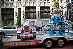 July 23 2012, Tokyo, Japan - A Hummer tows two robots in the streets of Shinjuku in Tokyo. The restaurant advertises that cost 10 billion yen (130 million) opening. Robots run by real women dressed in military, perform cabaret dance for its customers, opened in the Kabukicho area, Shinjuku in Tokyo. (Photo by Rodrigo Reyes Marin/AFLO)