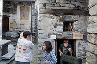 Switzerland. Canton Ticino. Corippo lies in the Verzasca valley. The stone houses are built from the local Ticino granite with stone roofs and have changed little for several hundred years. A family has rented a rustico (traditional house) for its holiday. Three generations. A grandmother carries her grandson, while her son (baby's father) holds a pram carriage in his hand. With a population of just 16, Corippo is the smallest municipality in Switzerland. Despite this, it possesses the trappings of communities many times its size such as its own coat of arms and a town council. A town council is a democratically elected form of government for small municipalities. A council may serve as both the representative and executive branch. The village has maintained its status as an independent entity since its incorporation in 1822. 9.05.13 © 2013 Didier Ruef