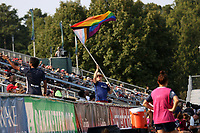 CARY, NC - SEPTEMBER 12: A member of the North Carolina Courage supporters group encourages the other fans while waiving a large rainbow flag during a game between Portland Thorns FC and North Carolina Courage at Sahlen's Stadium at WakeMed Soccer Park on September 12, 2021 in Cary, North Carolina.