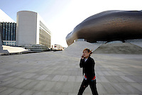 A lady speaks on mobile phone in front of the new museum in Kangbashi district of the Chinese city of Ordos, Inner Mongolia. 12-May-2011