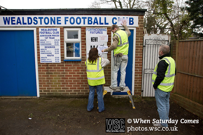 Wealdstone 0 Newport County 0, 17/03/2012. St Georges Stadium, FA Trophy Semi Final. Helpers putting up signs by the turnstiles outside St Georges Stadium, home ground of Wealdstone FC, before the club played host to Newport County in the semi-final second leg of the F.A. Trophy. The game ended in a goalless draw, watched by a capacity crowd of 2,092 which meant the visitors from Wales progressed by three goals to one to the competition's final at Wembley, where they would meet York City. The F.A. Trophy was the premier cup competition for non-League clubs in England and Wales affiliated to the Football Association. Photo by Colin McPherson.