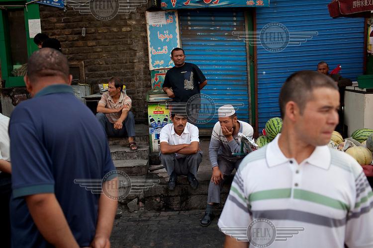 Uighur men sit on the street in the Uighur district of Urumqi.