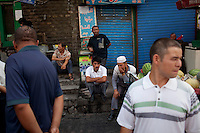 Uighur men sit on the street in the Uighur district of Urumqi.