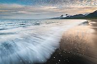 Landscape of waves washing up along the sandy beach of Katmai National Park, Aleutian mountain range, Alaska Peninsula, southwest Alaska.