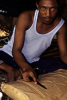 Abidjan, Ivory Coast, Cote d'Ivoire - Malian Tuareg Leatherworker Taher Saleh carves design into leather covering wooden storage chest.  Handicraftsmen travel around West Africa in search of tourists and visitors buying handicrafts to take home.