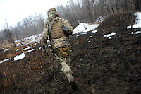 """UKRAINE, 02.2016, Oblast Donetsk. Ukrainian-Russian conflict concerning Eastern Ukraine / Foreign volunteers (""""Task Force Pluto"""") fighting with the far-right militia Pravyi Sektor against the Russian-backed separatists: Charlie (USA) runs under enemy fire across a muddy field on an ammunition re-supply mission. © Timo Vogt/EST&OST"""