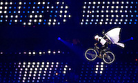 """27 JUL 2012 - LONDON, GBR - A performer dressed as a dove to represent a Dove of Peace attempts to cycle out of the Olympic Stadium during the """"Bike a.m."""" section of the Opening Ceremony of the London 2012 Olympic Games in the Olympic Park, Stratford, London, Great Britain (PHOTO (C) 2012 NIGEL FARROW)"""