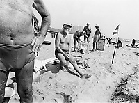 """USA. New York City. A group of old men with swimsuits are resting on the sandy beach in Coney Island. Towel with a penguin. An american flag. The national flag of the United States of America, often simply referred to as the American flag, consists of thirteen equal horizontal stripes of red (top and bottom) alternating with white, with a blue rectangle in the canton (referred to specifically as the """"union"""") bearing fifty small, white, five-pointed stars arranged in nine offset horizontal rows of six stars (top and bottom) alternating with rows of five stars. The 50 stars on the flag represent the 50 states of the United States of America and the 13 stripes represent the thirteen British colonies that declared independence from the Kingdom of Great Britain and became the first states in the Union. Nicknames for the flag include the """"Stars and Stripes"""", """"Old Glory"""", and """"The Star-Spangled Banner"""". © 1985 Didier Ruef"""