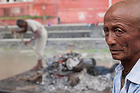 A relative stands in front of a burning body at burning ghats near Pashupati Nath temple in Kathmandu, Nepal