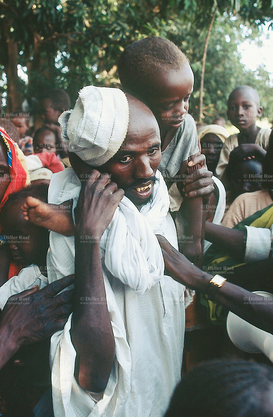 Sudan. West Darfur. Kerenek. The non-governmental organization (ngo) Médecins sans Frontières (MSF) Switzerland distributes food to family whose children have a height below one meter and 10. A father carries his son on the shoulders in order to avoid the child being suffocated in the crowd. © 2004 Didier Ruef