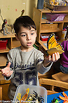 Education Preschool 3-4 year olds boy holding up toy butterfly model talking to himself