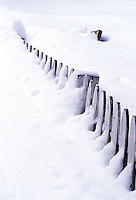 Wooden fence poking through top of snow<br />