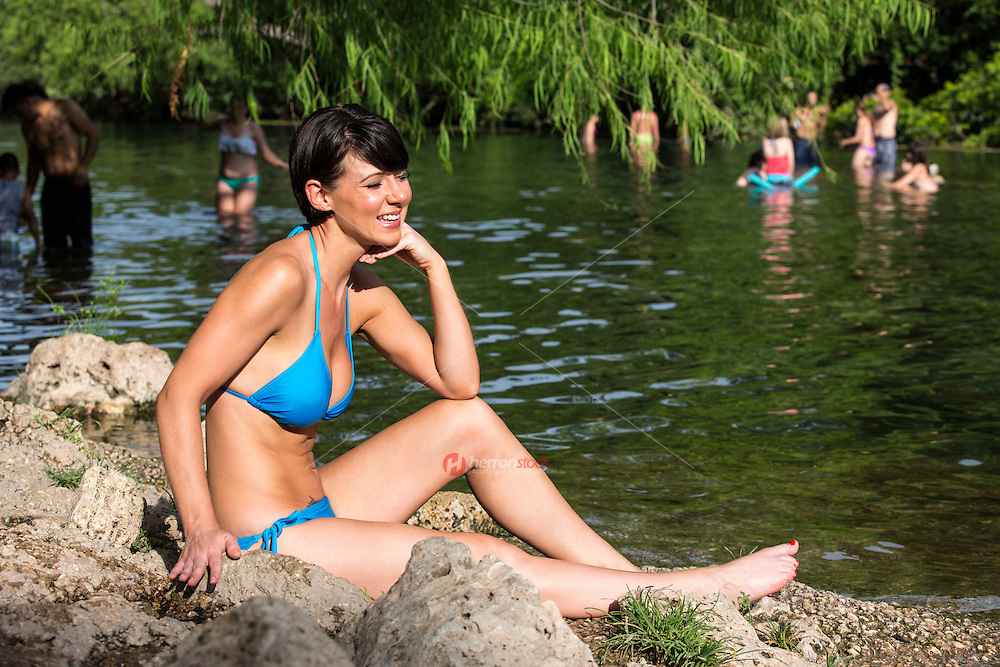 Smiling modern female sunbathing during summer at Barton Creek, a scenic Austin swimming hole and spring-fed creek feeding into Lady Bird Lake.
