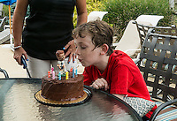 Boy blows out the candles on a birthday cake adorned with a soccer player figure.