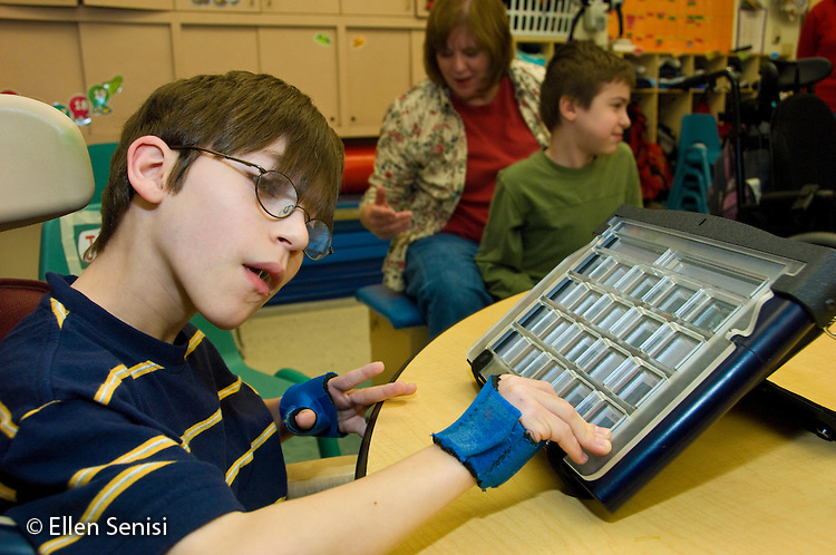 MR / Albany, NY.Langan School at Center for Disability Services .Ungraded private school which serves individuals with multiple disabilities.Student (boy, 9, cerebral palsy, limited verbal output with expressive and receptive language delays) uses alternative and augmentative communication device during speech and language development lesson. He is wearing hand splints to help him isolate his thumbs which helps him use the device more easily..MR: Rub1.© Ellen B. Senisi