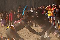 Lutadores de diversas aldeias, jovens e adultos lutam o Huka-huka.<br /> <br /> Huka-hukaLuta corporal que na terminologia kamaiurá lembra os gritos dos lutadores ao se defrontarem imitando o rugido da onça. Os anfitriões enfrentam uma aldeia convidada de cada vez, começando por lutas individuais de campeões reconhecidos. Seguem-se lutas simultâneas de vários pares de rivais, até as lutas dos muito jovens. Os lutadores se defrontam batendo o pé direito no chão, dando voltas no sentido dos ponteiros do relógio, com o braço esquerdo estendido e o direito retraído, enquanto gritam alternadamente: hu! ha! hu! ha! Até que chocam as mãos direitas e enlaçam o pescoço do adversário com a esquerda. A luta, que pode durar poucos segundos, termina quando um dos adversários é derrubado, o que não tem que ocorrer literalmente, bastando que a parte posterior de um de seus joelhos seja agarrada pela mão do outro, o que é considerado condição suficiente para provocar-lhe a queda. As aldeias convidadas não lutam entre si. Os enfeites dos troncos do Kwarup podem ser dados aos lutadores vencedores e também aos dois tocadores de maracá.<br /> <br /> Fonte: ISA<br /> <br /> Querência, Mato Grosso, Brasil. <br /> 26/07/2015