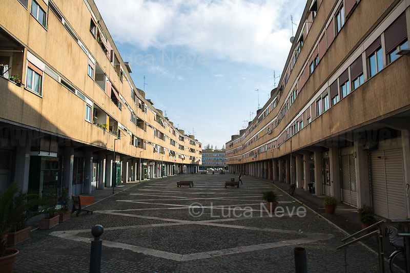 Piazza Grecia.<br /> <br /> Rome, 18/03/2020. Rome's Olympic Village district under the Italian Government lockdown for the Outbreak of the Coronavirus SARS-CoV-2 - COVID-19. On the 22nd March, the Italian PM Giuseppe Conte signed a new Decree Law which suspends non-essential industry productions and contains the list of allowed working activities, which includes Pharmaceutical & food Industry, oil & gas extraction, clothes & fabric, tobacco, transports, postal & banking services (timetables & number of agencies reduced), delivery, security, hotels, communication & info services, architecture & engineer, IT manufacturers & shops, call centers, domestic personnel (1.).<br /> Updates: Italy: 22.03.20, 6:00PM: 46.638 positive cases; 7.024 recovered; 5.476 died.<br /> <br /> The Rome's Olympic Village (1957-1960) was designed by: V. Cafiero, A. Libera, A. Luccichenti, V. Monaco, L. Moretti. «Built to host the approximately 8,000 athletes involved in the 1960 Olympic Games, Rome's Olympic Village is a residential complex located between Via Flaminia, the slopes of Villa Glori and Monti Parioli. It was converted into public housing [6500 inhabitants, ndr] at the end of the sporting event. The intervention is an example of organic settlement, characterized by a strong formal homogeneity, consistent with the Modern Movement's principles of urbanism. The different architectural structures are made uniform by the use of some common elements: the pilotis, ribbon windows, concrete stringcourses, and yellow brick curtain covering. At the center of the neighborhood, the Corso Francia viaduct - a road bridge about one kilometer long - was built by Pier Luigi Nervi […]» (2.).<br /> <br /> Info about COVID-19 in Italy: http://bit.do/fzRVu (ITA) - http://bit.do/fzRV5 (ENG)<br /> 1. March 22nd Decree Law http://bit.do/fFwJn (ITA)<br /> 2. (Atlantearchitetture.beniculturali.it MiBACT, ITA - ENG) http://bit.do/fFw3H<br /> 12.03.20 Rome's Lockdown for the Outbreak of the Coronavirus SARS
