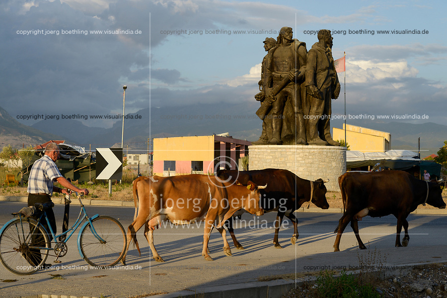 ALBANIA, Shkodra, farmer with cows infront of memorial Five Heroes which was created in 1984 by Shaban Hadëri, to celebrate the sacrifice of five partisans from Vig, who lost their lives in 1944, fighting against the Nazi collaborationist gangs / ALBANIEN, Shkoder, Bauer mit Kuehen vor Fuenf Helden Denkmal
