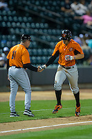 Conor Bierfeldt (right) of the Frederick Keys shakes hands with third base coach Keith Bodie (11) after hitting a home run against the Winston-Salem Dash at BB&T Ballpark on May 24, 2016 in Winston-Salem, North Carolina.  The Keys defeated the Dash 7-1.  (Brian Westerholt/Four Seam Images)