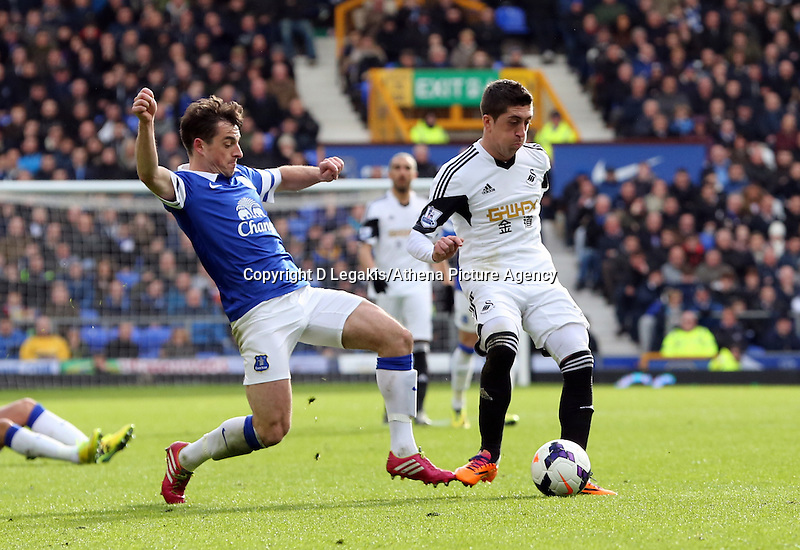 Pictured: Pablo Hernandez of Swansea (R) is challenged by Leighton Baines of Everton (L). Saturday 22 March 2014<br /> Re: Barclay's Premier League, Everton v Swansea City FC at Goodison Park, Liverpool, UK.